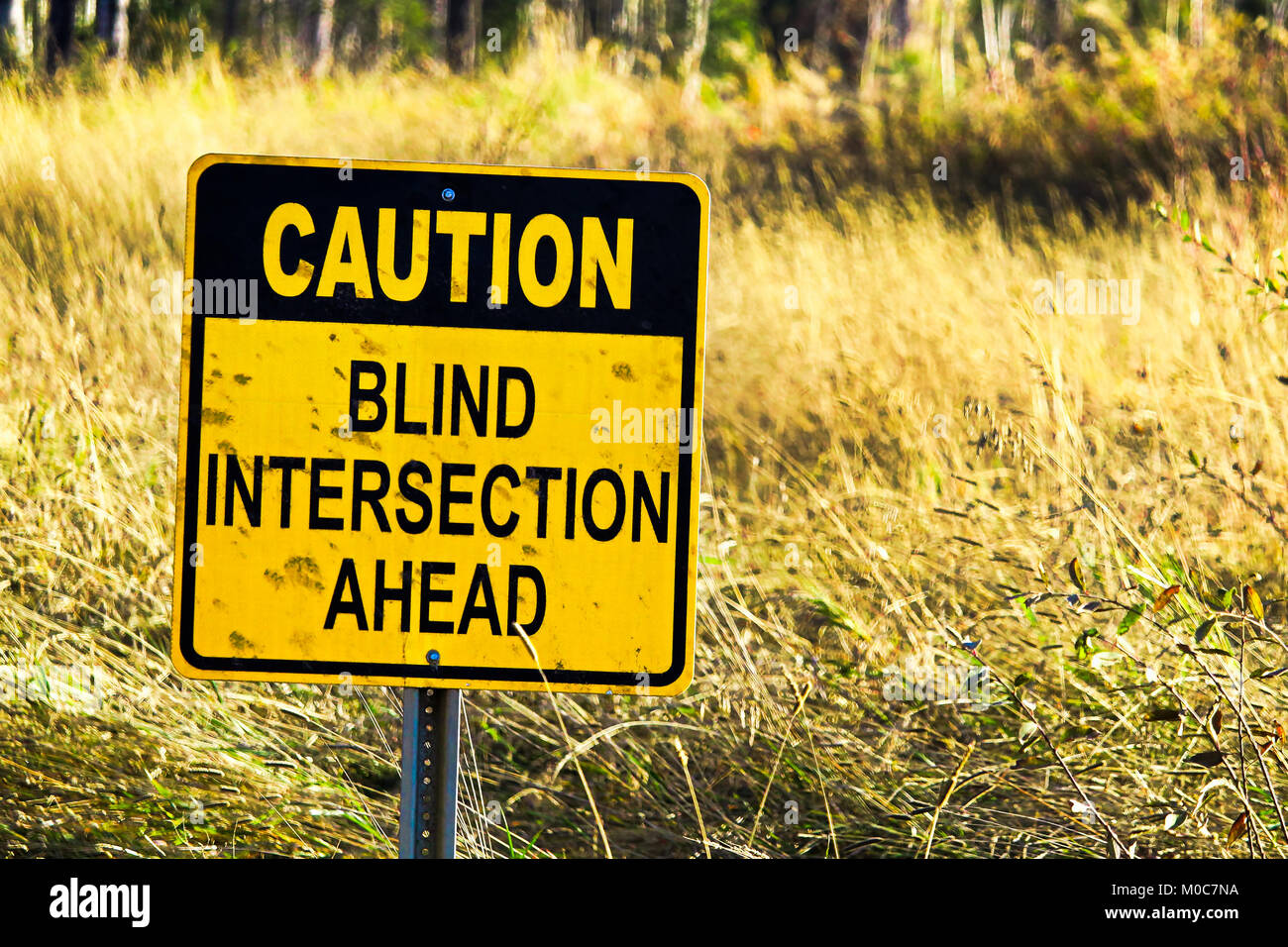 Closeup of a Caution Blind Intersection Ahead sign - Stock Image