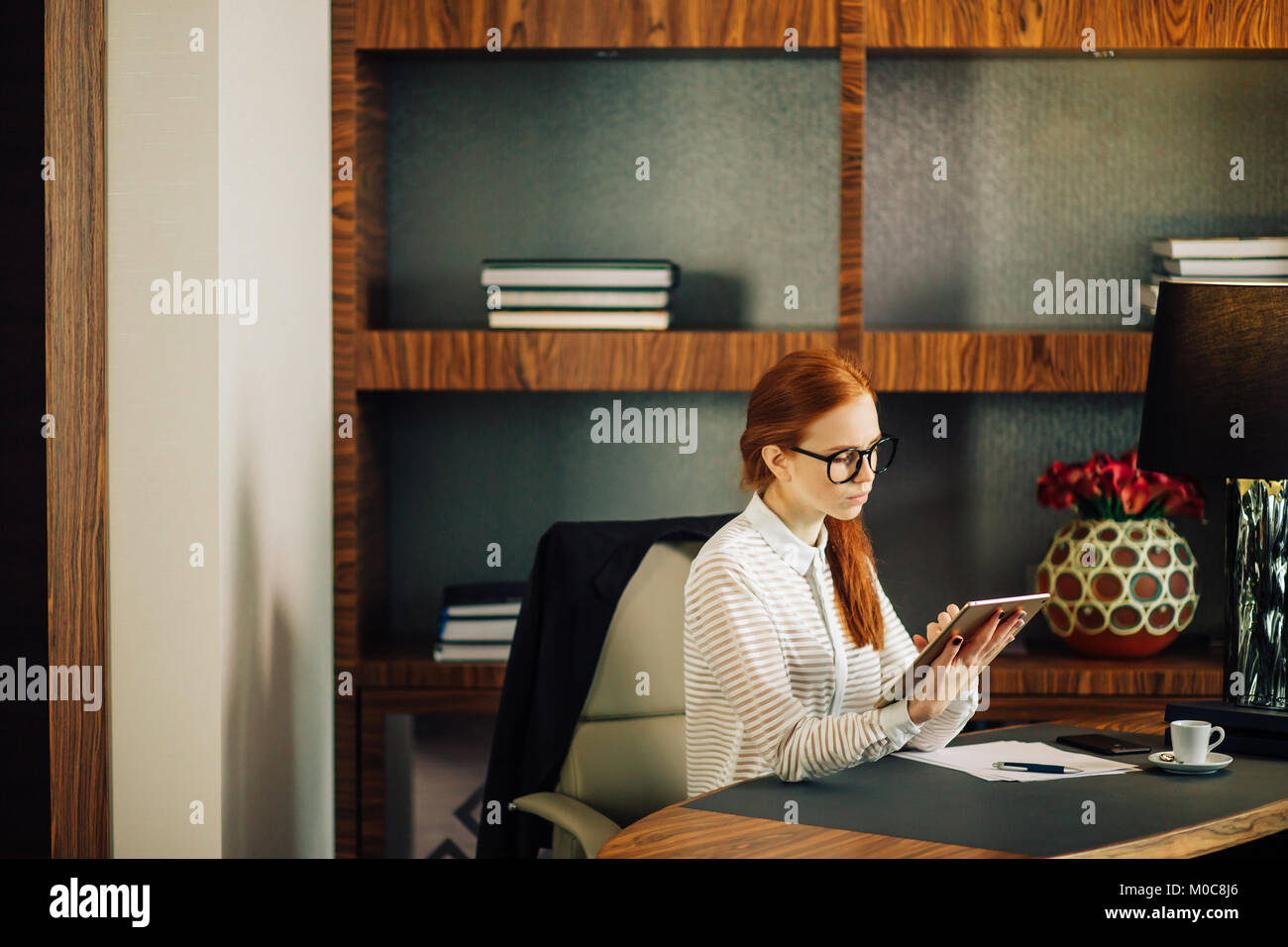 Businesswoman wearing glasses using digital tablet in office - Stock Image