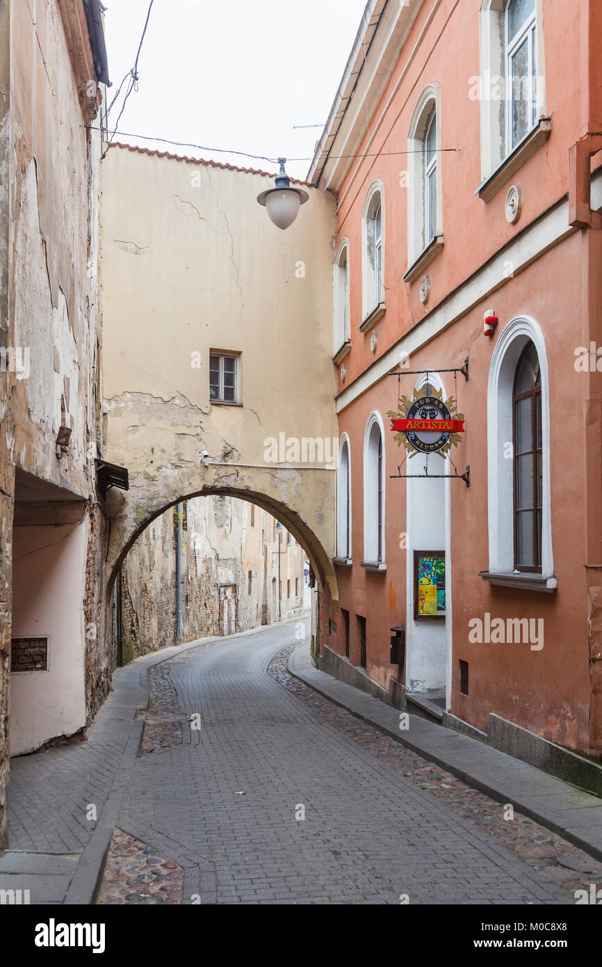 The narrow Sv Kazimiero Gatve with old dilapidated arch built over the road in the Old Town of Vilnius, capital - Stock Image