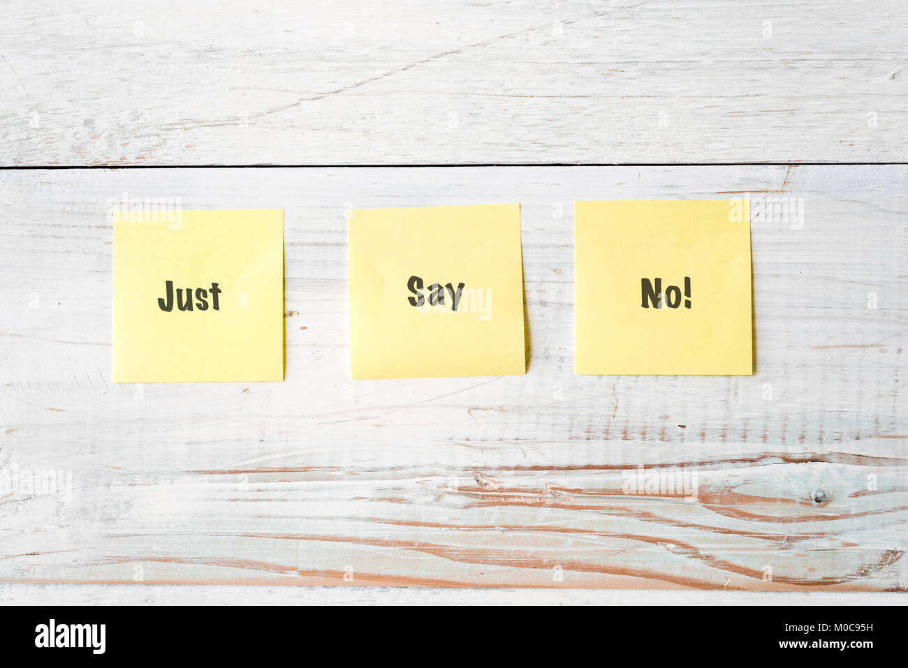 three yellow Post It notes with message Just Say No! against weathered white wood background - Stock Image
