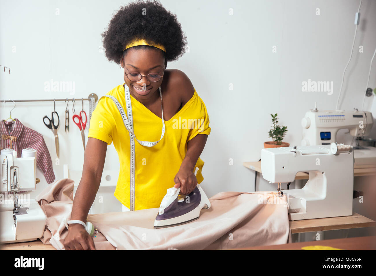 african Woman seamstress Ironing cloth - Stock Image