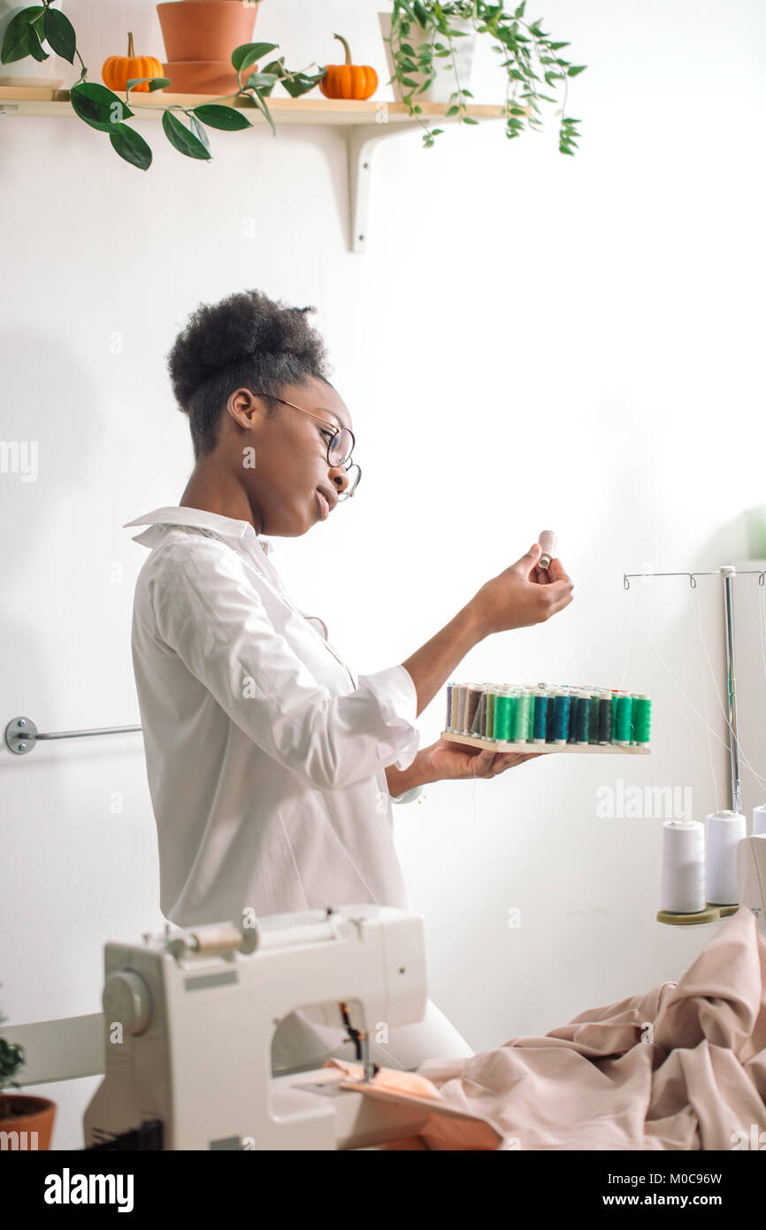 african seamstress holding coils with threads - Stock Image