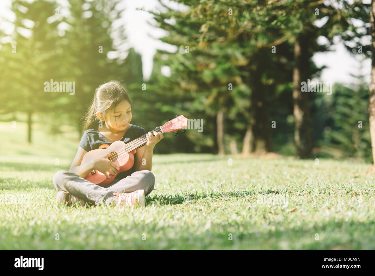 young and happy asian girl playing with ukelele guitar at the park in sunny morning. hobbies and tranquility concept - Stock Image