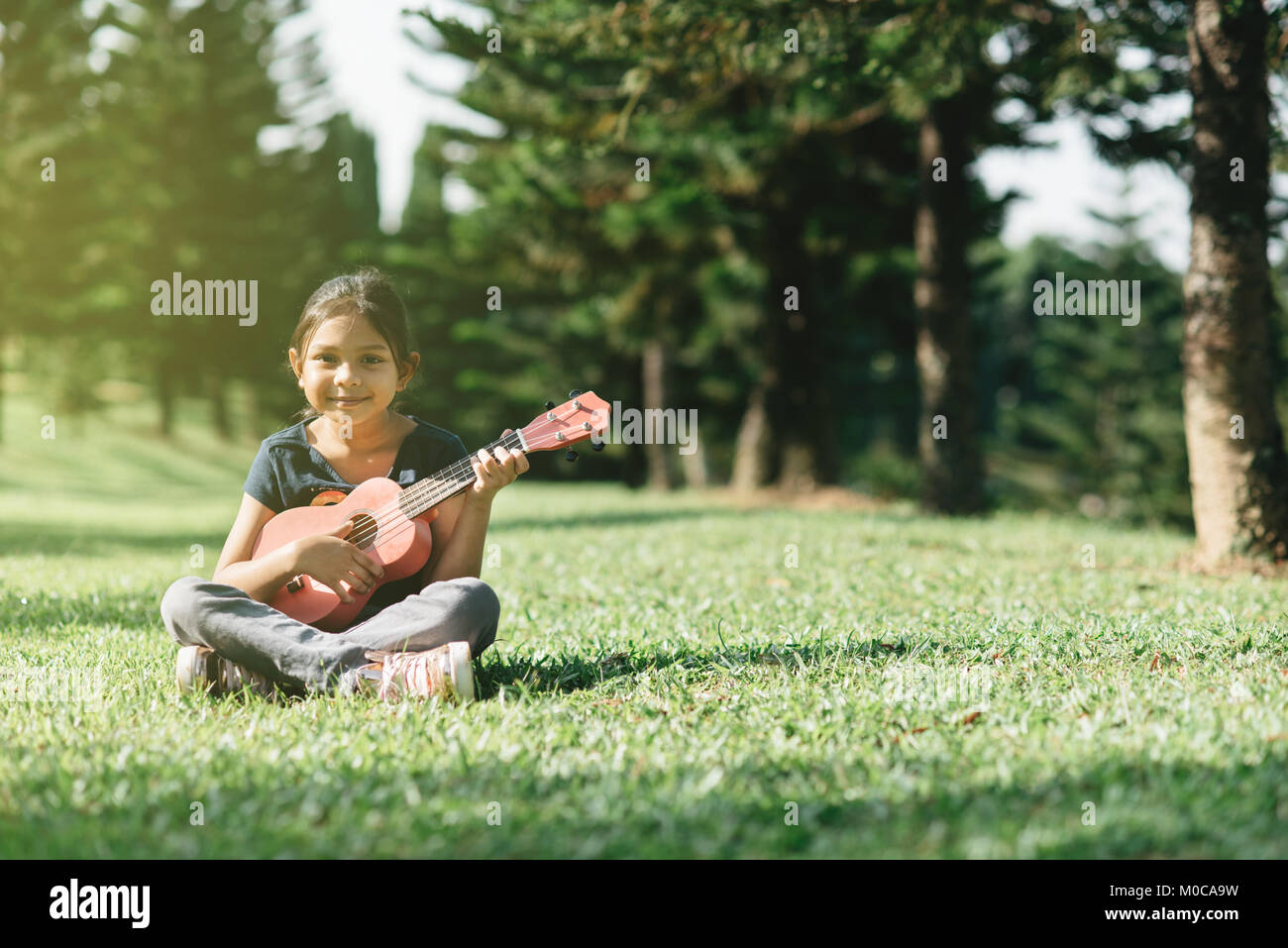 young and happy asian girl playing ukelele guitar in the park at sunny morning while looking at camera. hobbies - Stock Image