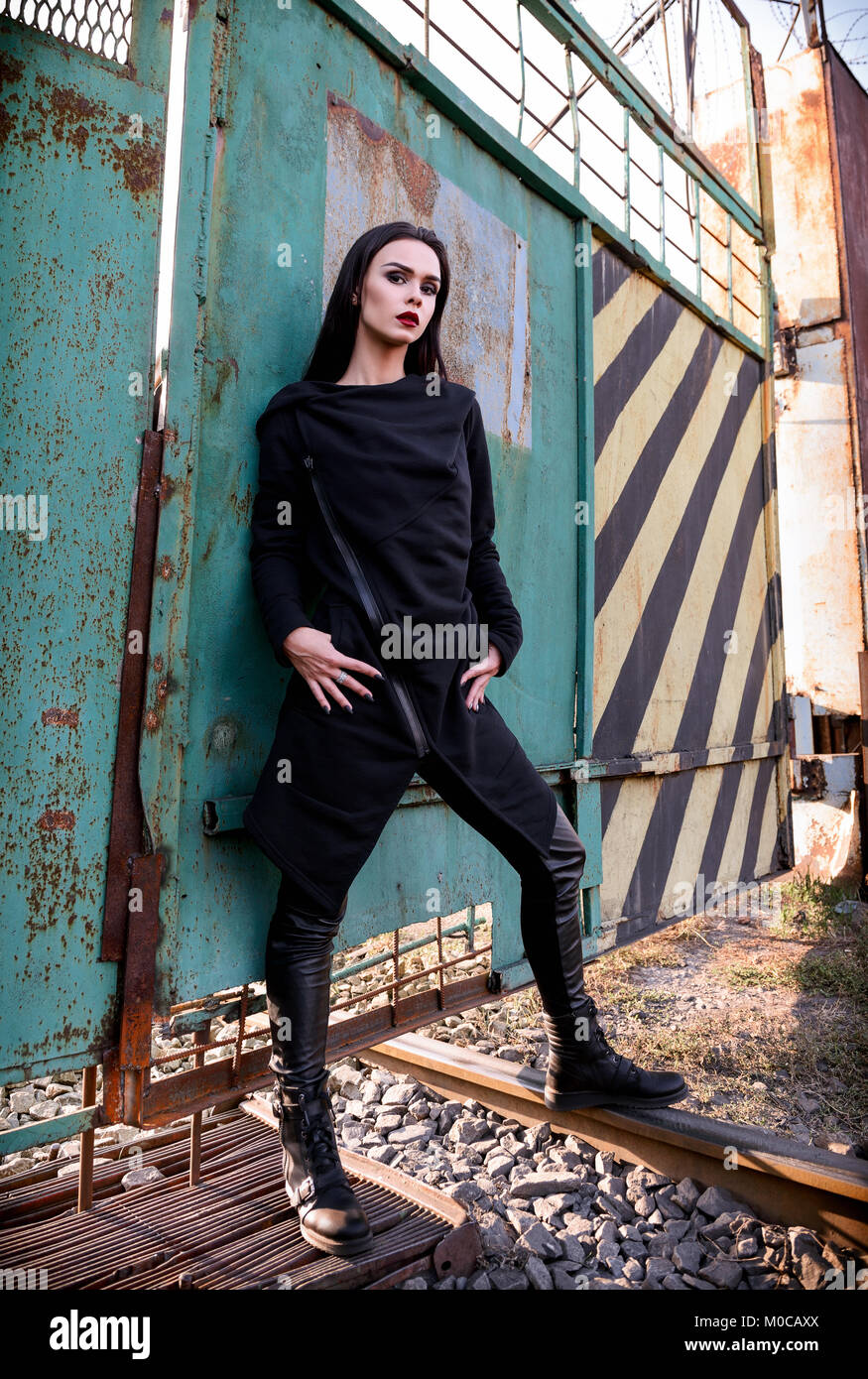 Fashion shot: portrait of the beautiful rock girl (informal model) in tunic and leather pants standing at metallic - Stock Image