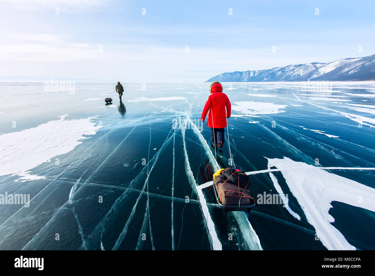 Woman with a sledge walk is on the ice of Lake Baikal. - Stock Image