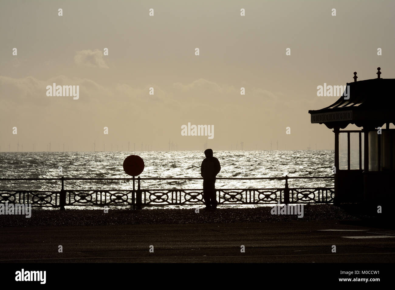 A man in a hooded top silhouetted against the ocean on Hove seafront - Stock Image