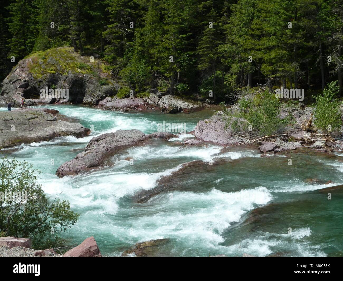 Greenish blue fast moving water, better known as white water or rapids swiftly rush down stream.  A great water - Stock Image