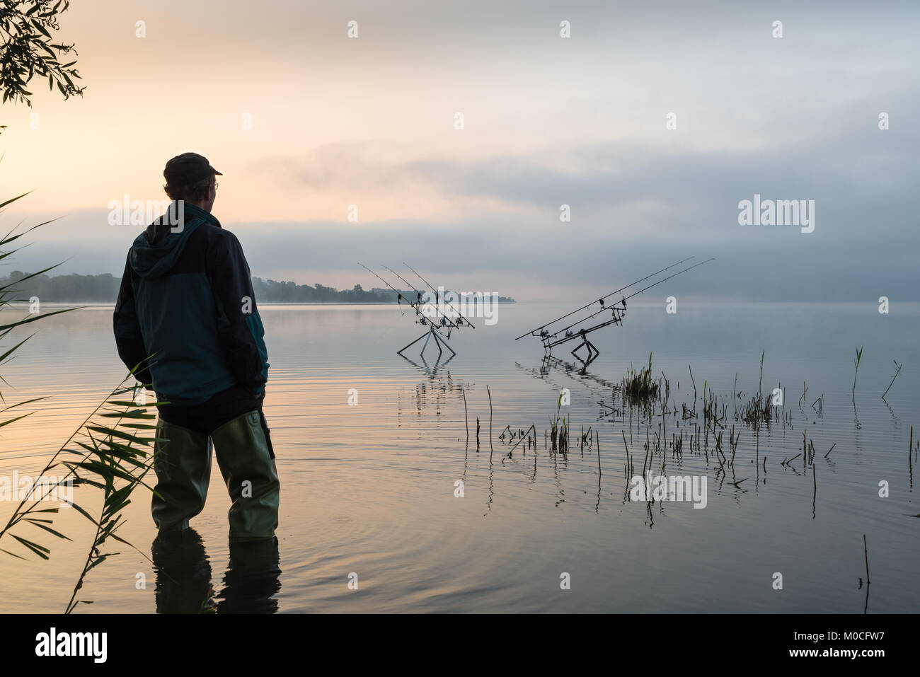 Fishing adventures, carp fishing. Early morning with mist and fisherman with high rubber boots - Stock Image