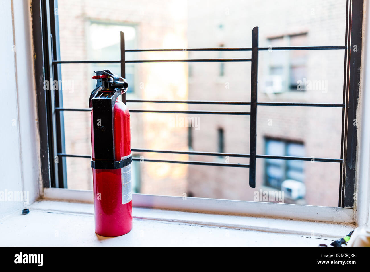 Small apartment red fire extinguisher safety by window in New York City NYC urban Bronx, Brooklyn brick housing, - Stock Image