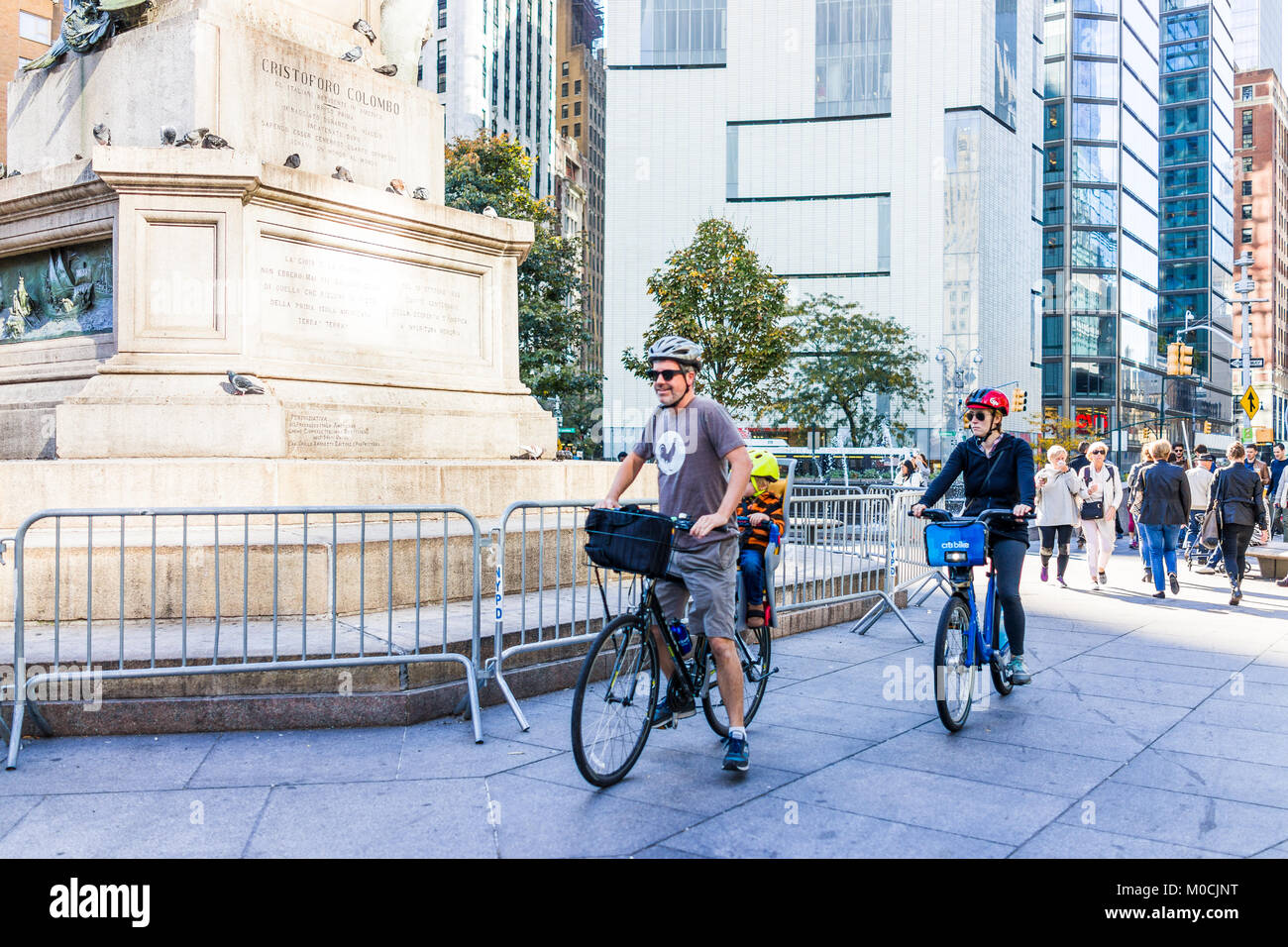 New York City, USA - October 28, 2017: Midtown Manhattan with people riding bicycles walking by Christopher Columbus Stock Photo