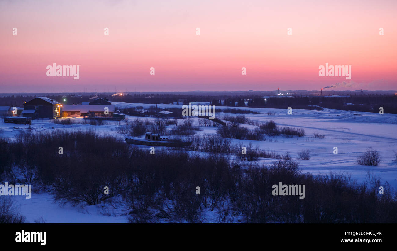 Magnificent winter sunrise in Narian-Mar with snow covered river fir forest and tundra. Great outdoor scene, natural - Stock Image