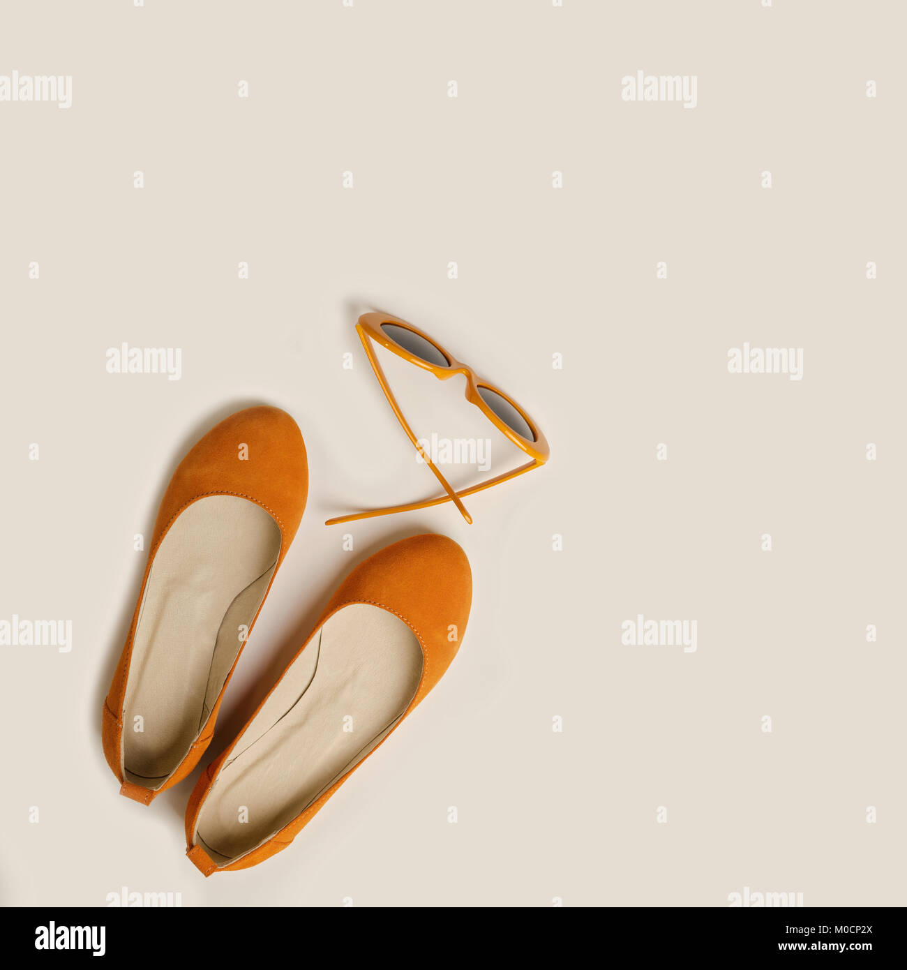 Fashion accessories for the beach - shoes and orange glasses  on a white background. Selective focus. - Stock Image
