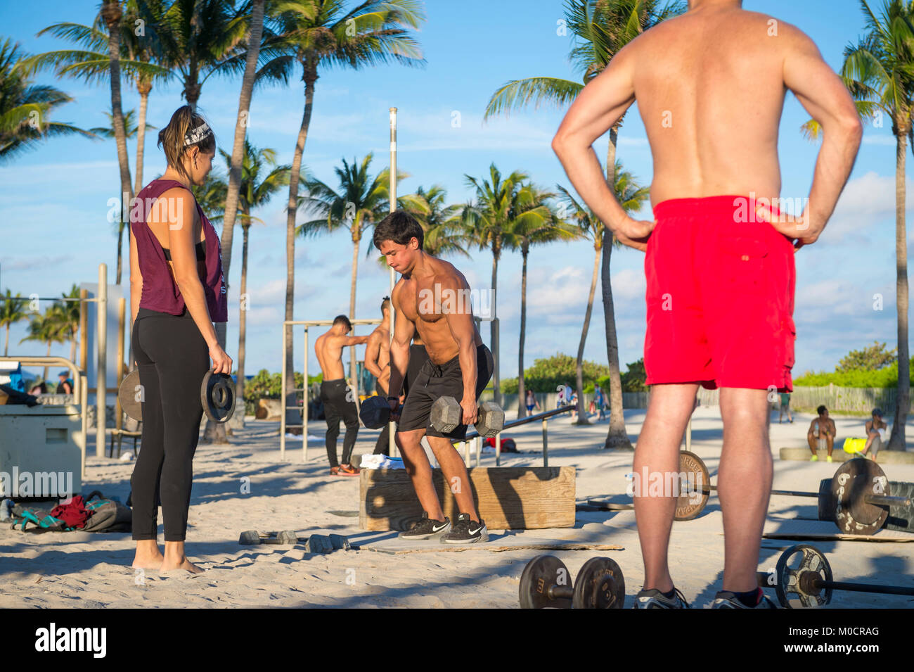 MIAMI - DECEMBER 29, 2017: Muscular young men and women work out in the outdoor gym known as Muscle Beach in Lummus - Stock Image