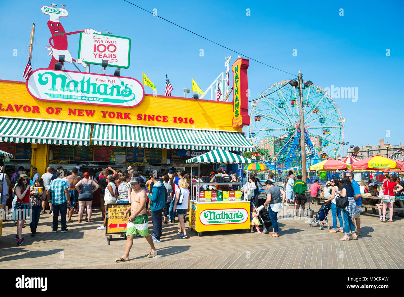 NEW YORK CITY - AUGUST 20, 2017: Visitors crowd the iconic wooden Coney Island boardwalk outside the famous Nathan's - Stock Image