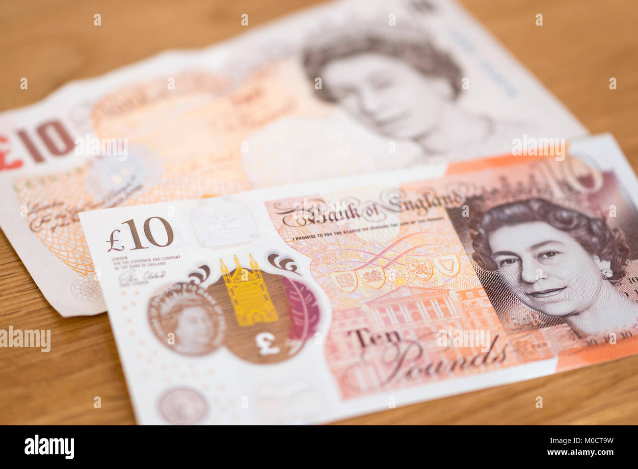 A new polymer £10 note overlaying an old paper £10 note - Stock Image