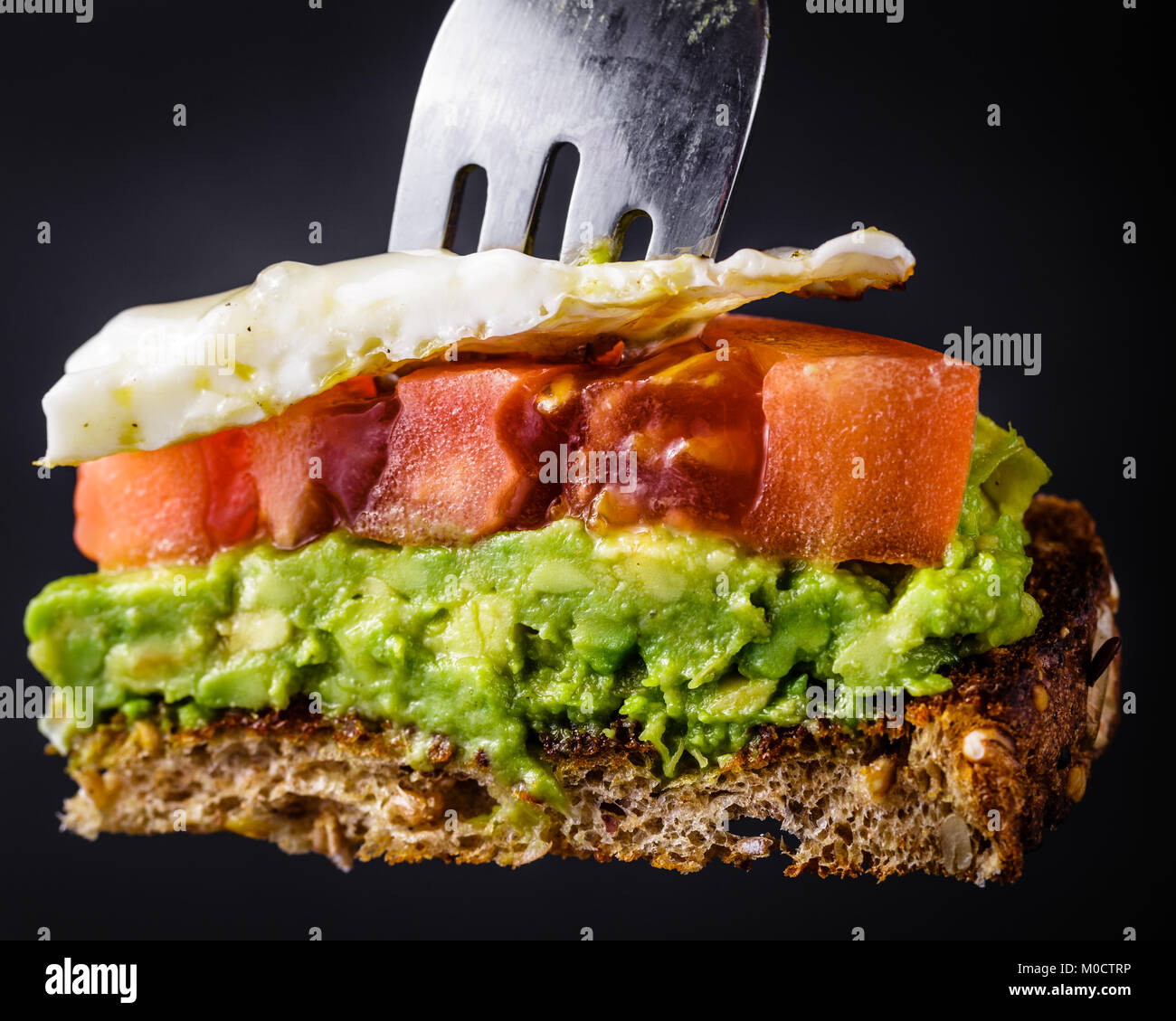 Bite sized piece of avocado toast with tomato and a fried egg on a fork.  Isolated on a black background - Stock Image