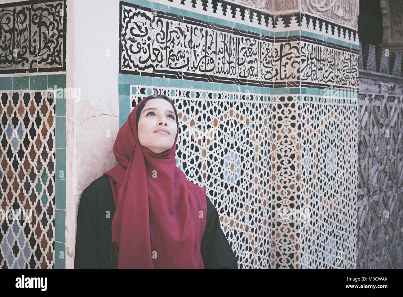 Arab woman in traditional clothing with red hijab in front of the wall with text from Koran - Stock Image