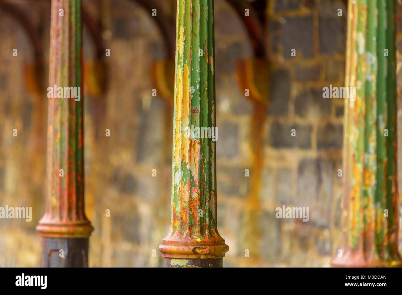 Cast iron support poles rusting in a line. - Stock Image