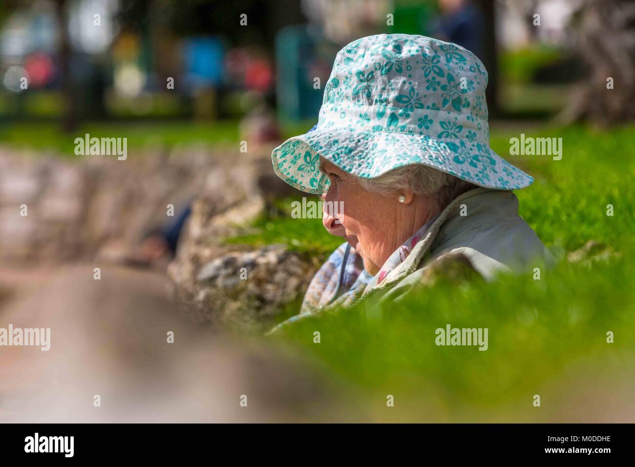 An old retired lady sitting in the sun with her sun hat on. - Stock Image