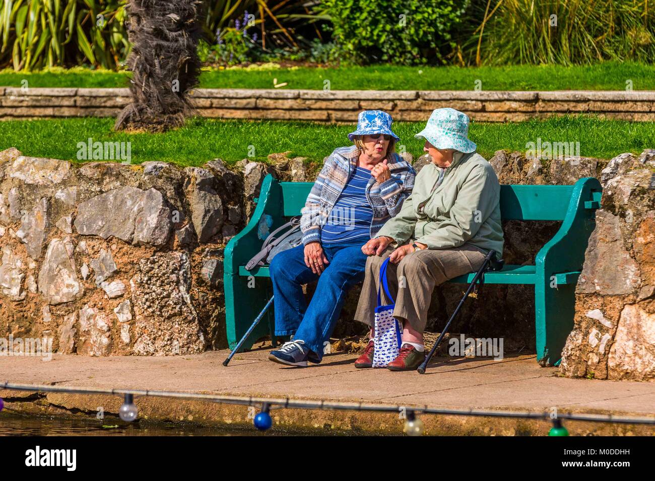 Two women friends chat together on a garden or park bench. - Stock Image