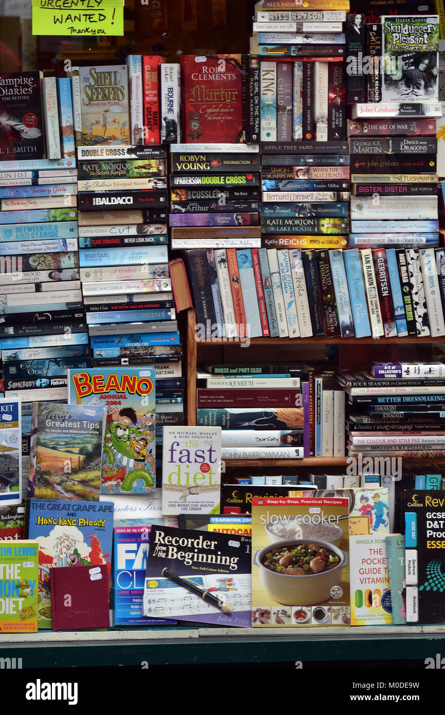 a large quantity or selection of paperback and hardback used or secondhand books in the window of a used book shop - Stock Image
