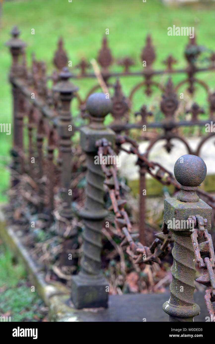 rusty or corroded decorative chains and cast iron railings around a tomb or grave in a churchyard or cemetery. decorative - Stock Image