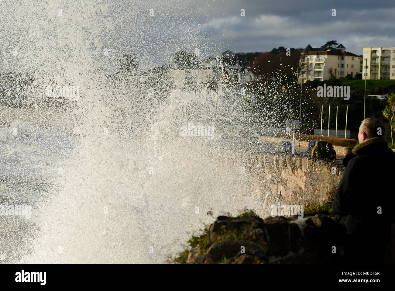 People watching from a safe location as waves crash against the sea wall during a stormy high tide at Torquay. - Stock Image