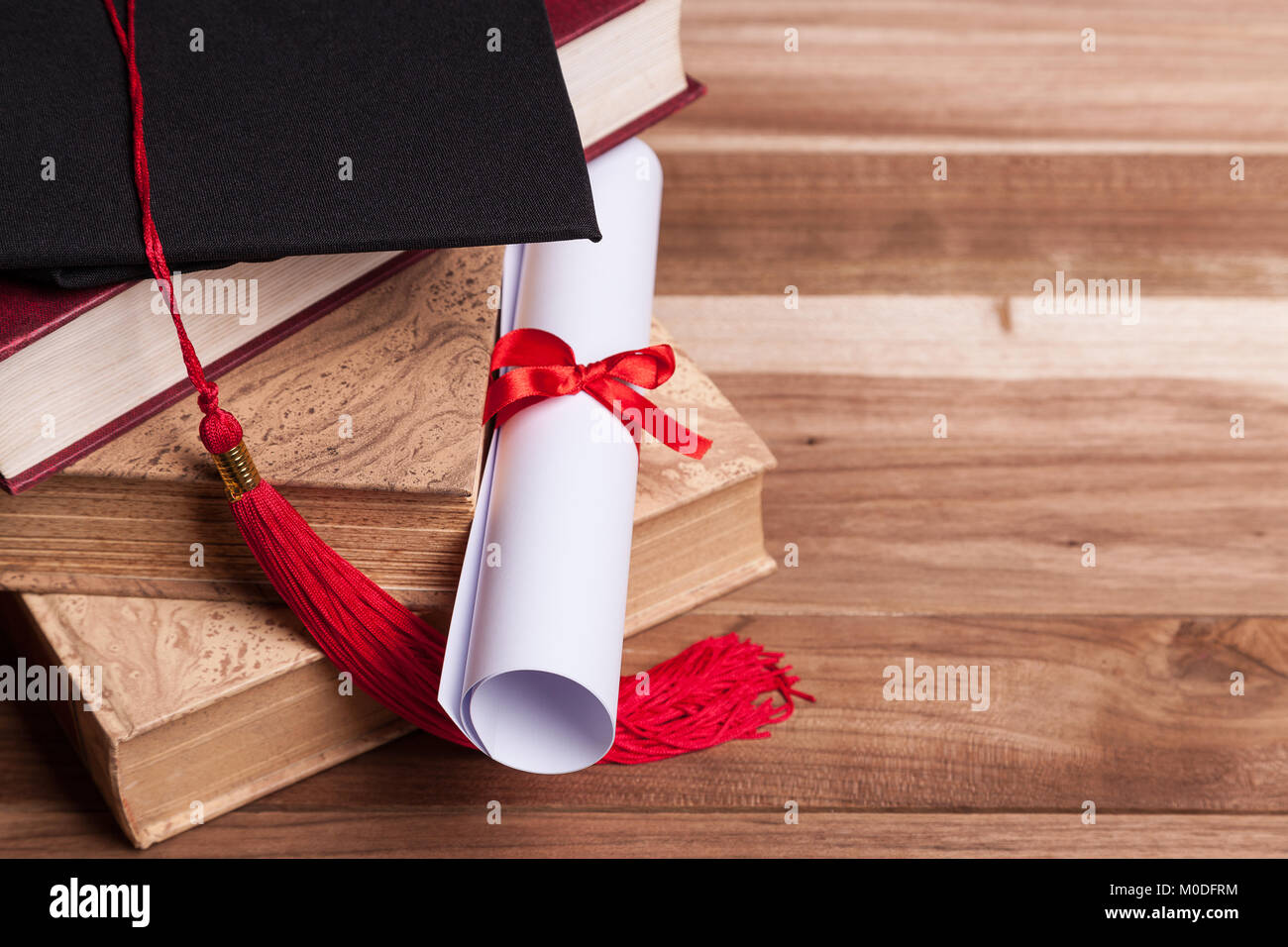 Black graduation cap and diploma on a stack of books - Stock Image
