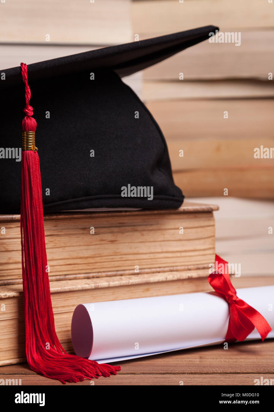 Mortarboard with red tassel, diploma, and books on a table - Stock Image
