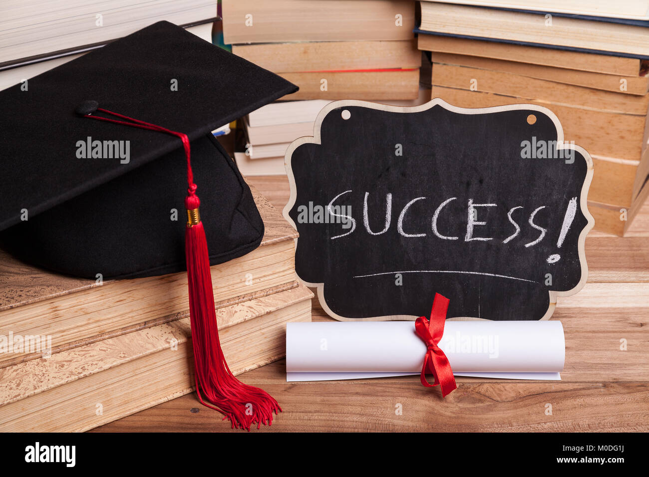 Little blackboard next to a diploma, some books, and a black mortarboard with red tassel. - Stock Image