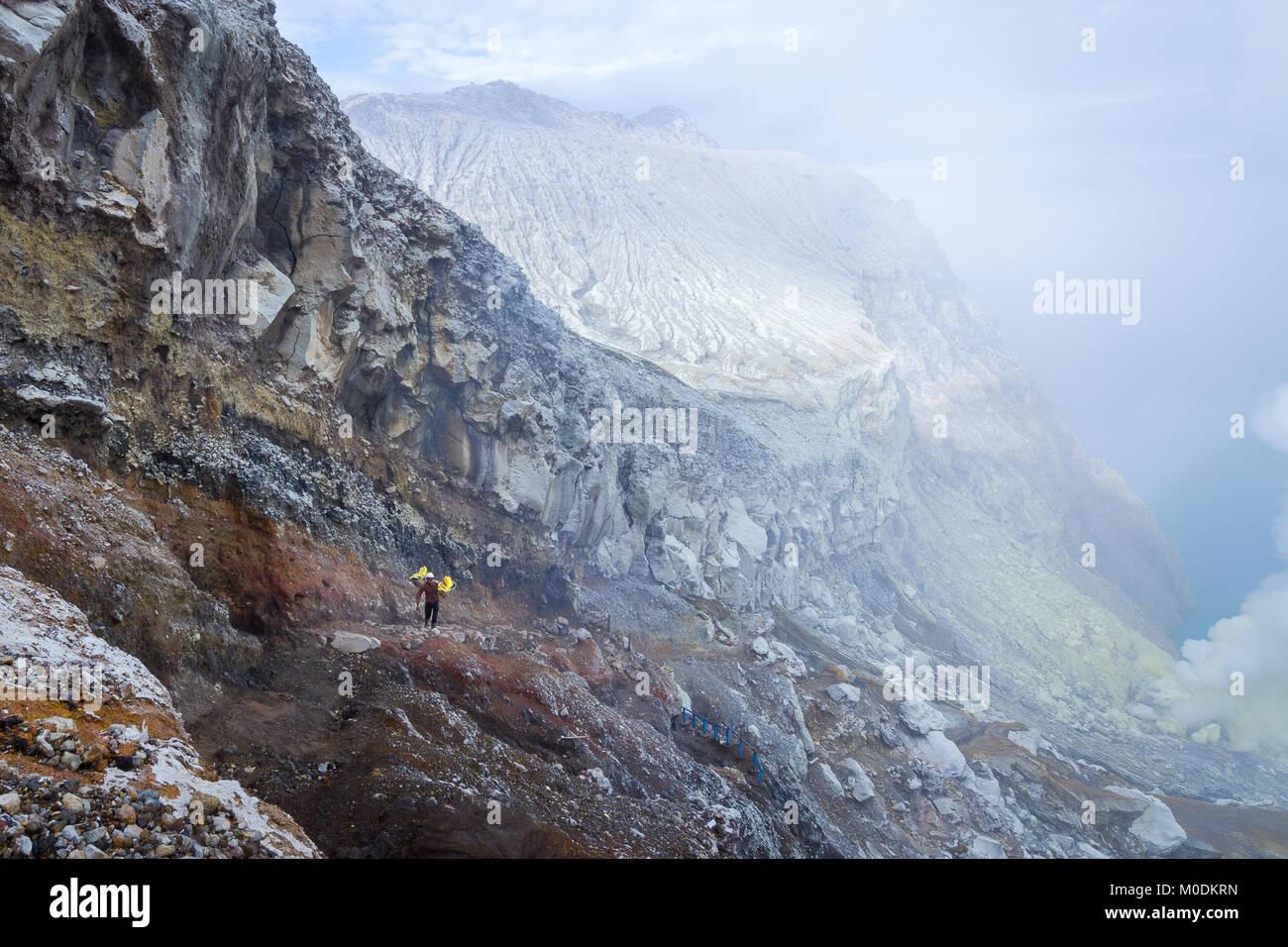 Sulfur miner in Mount Ijen (Kawah Ijen) - Stock Image