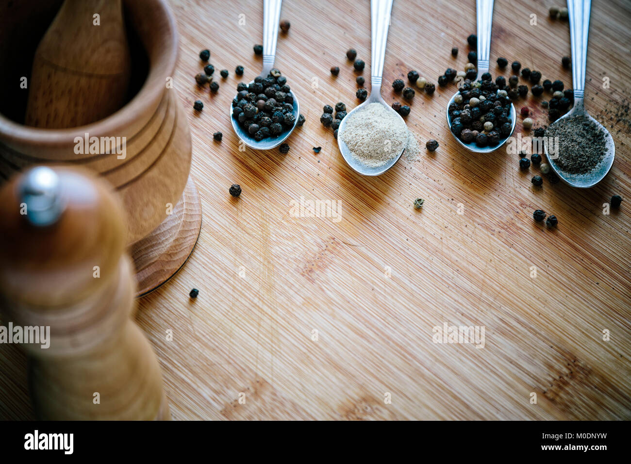 Various types of pepper on a wooden background - Stock Image