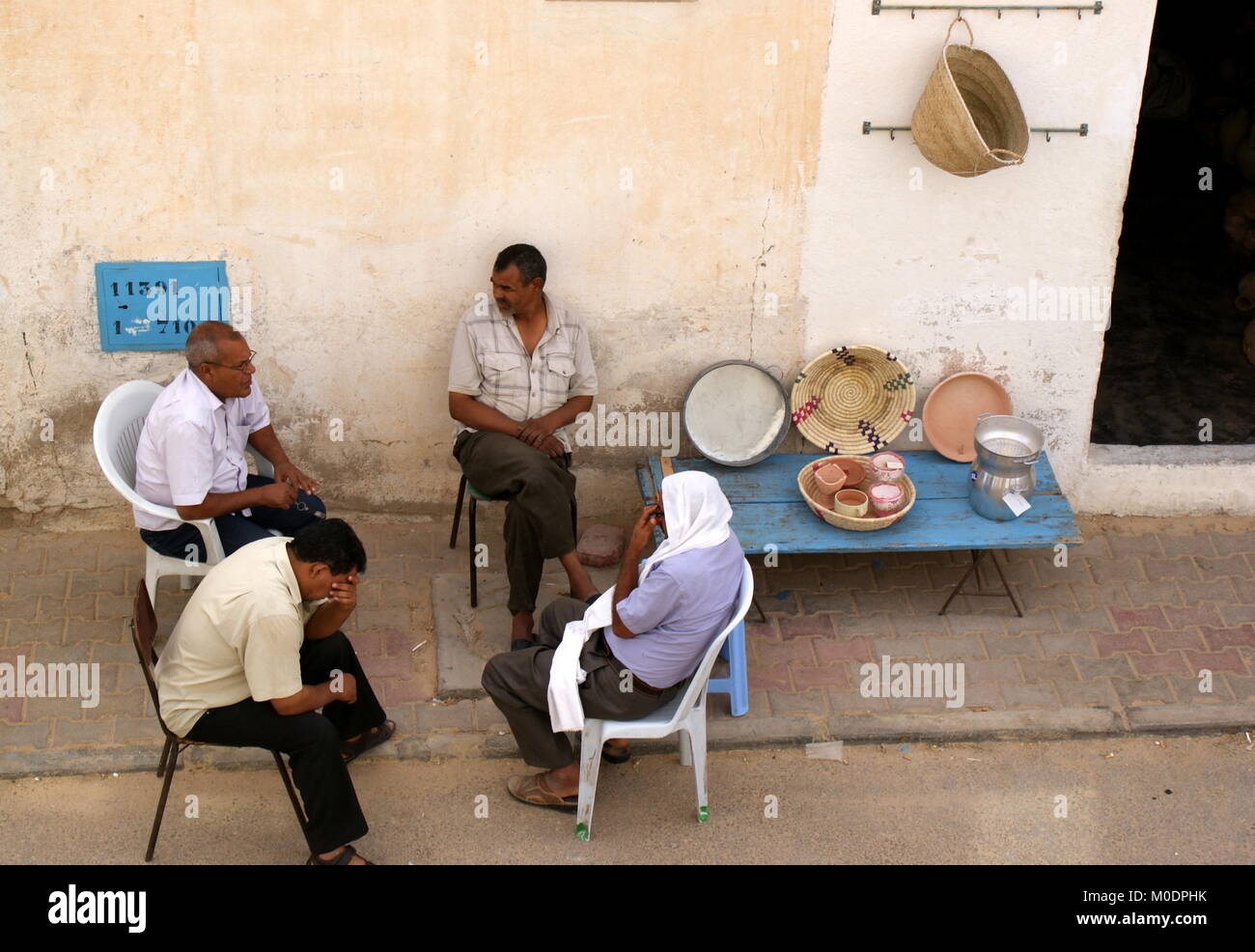 Four men sitting and chatting on the roadside next to a table with a few items for sale, Douz, Kebili district, - Stock Image