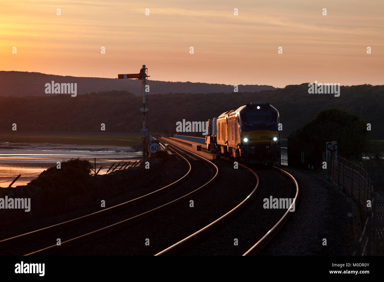 2 Direct Rail Services class 68 locomotives cross Arnside viaduct at sun set with a   nuclear Flask train - Stock Image