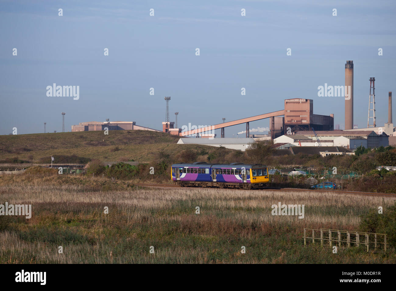Northern rail class 142 pacer train passing Cottam Marsh, Redcar  with the abandoned steelworks behind working the - Stock Image