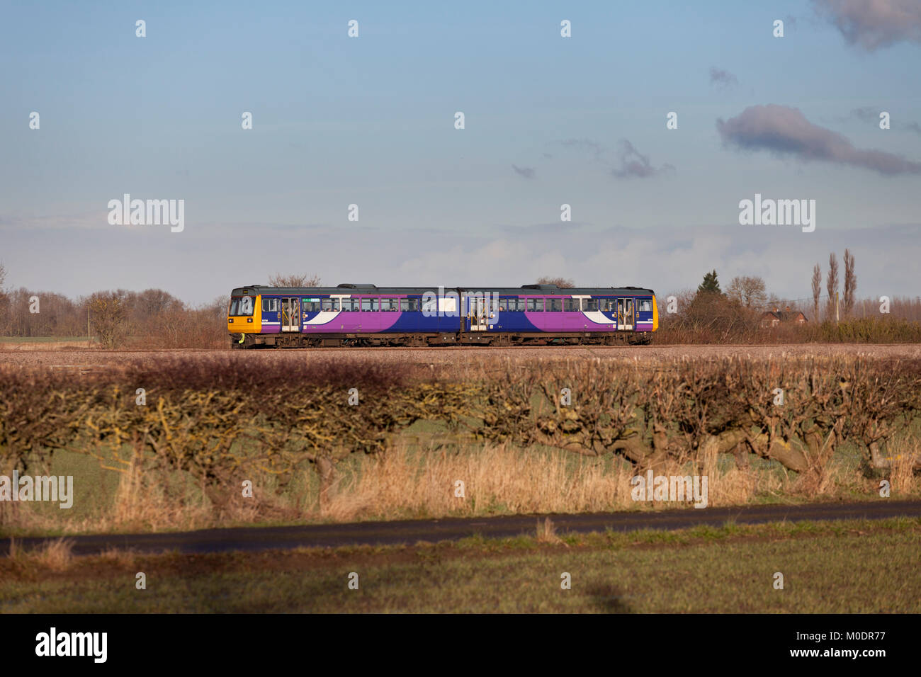A Northern rail class 142 pacer train passing Teesside Airport - Stock Image