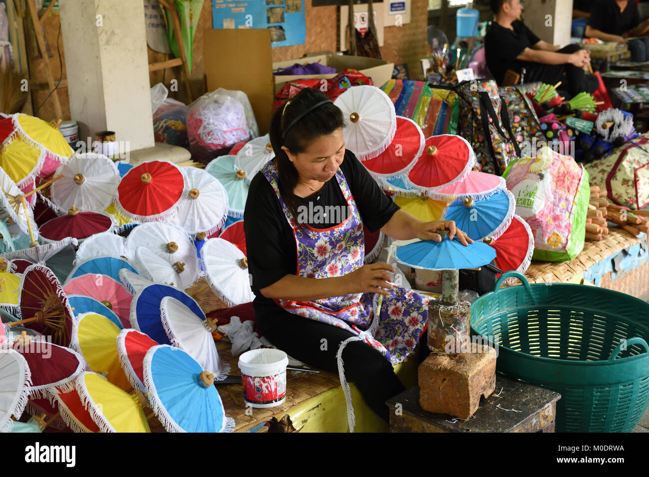 Thai woman worker attaching the frill to a paper umbrella at the Umbrella Making Centre, Bo Sang, Chiang Mai Province, Stock Photo