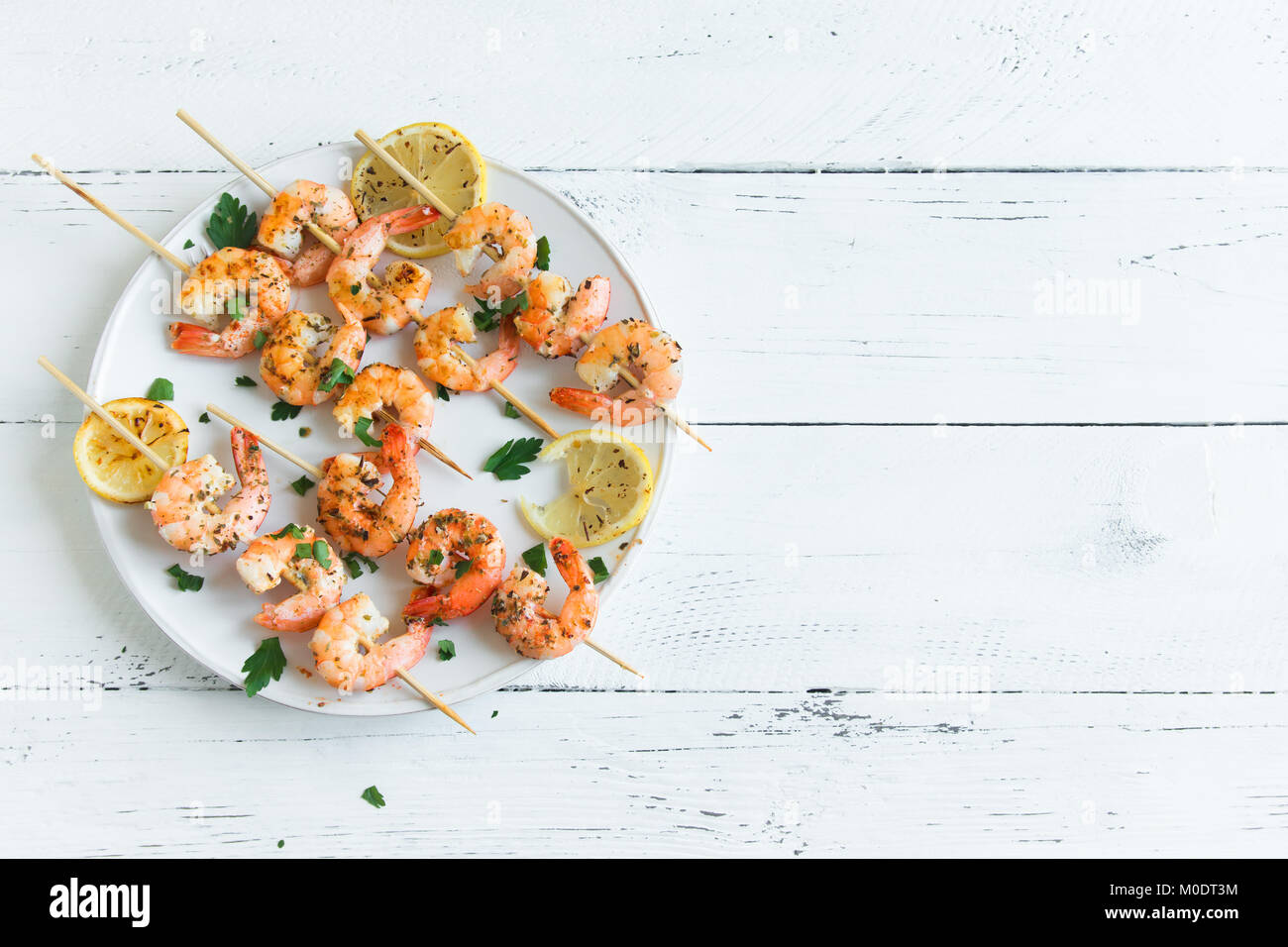 Grilled shrimp skewers. Seafood, shelfish. Shrimps Prawns skewers with spices and fresh herbs on white wooden background, - Stock Image
