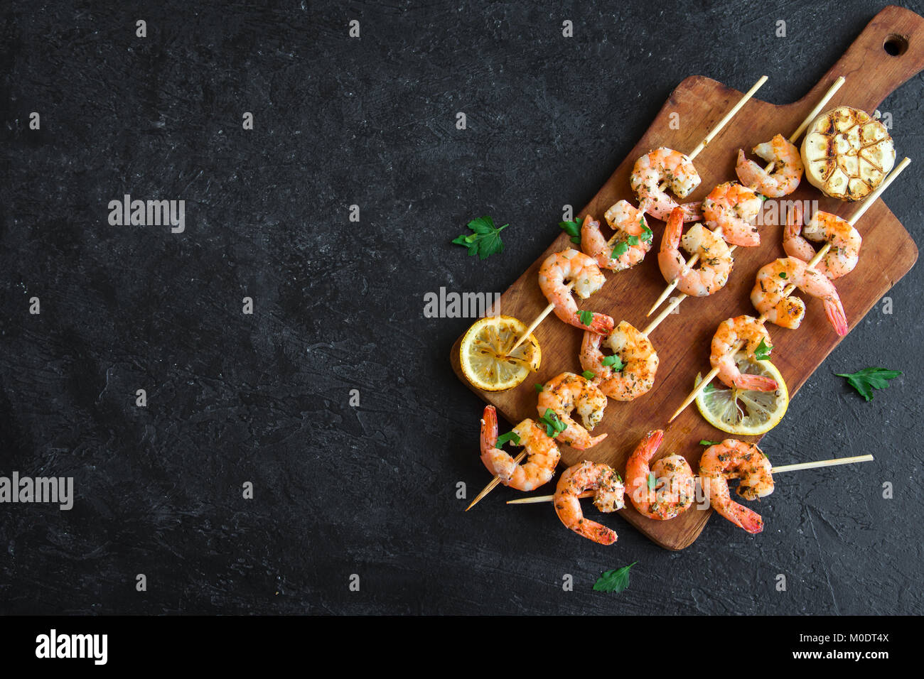 Grilled shrimp skewers. Seafood, shelfish. Shrimps Prawns skewers with herbs, garlic and lemon on black stone background, - Stock Image