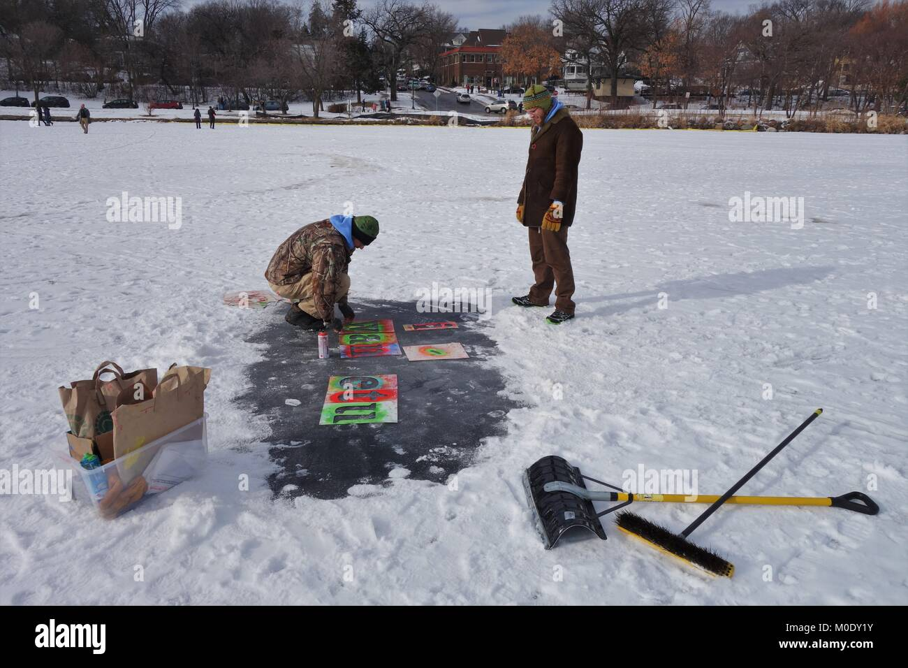 An artist spray painting Dakota Indian words on the ice, at the Art Shanty Projects on frozen Lake Harriet in Minneapolis, - Stock Image