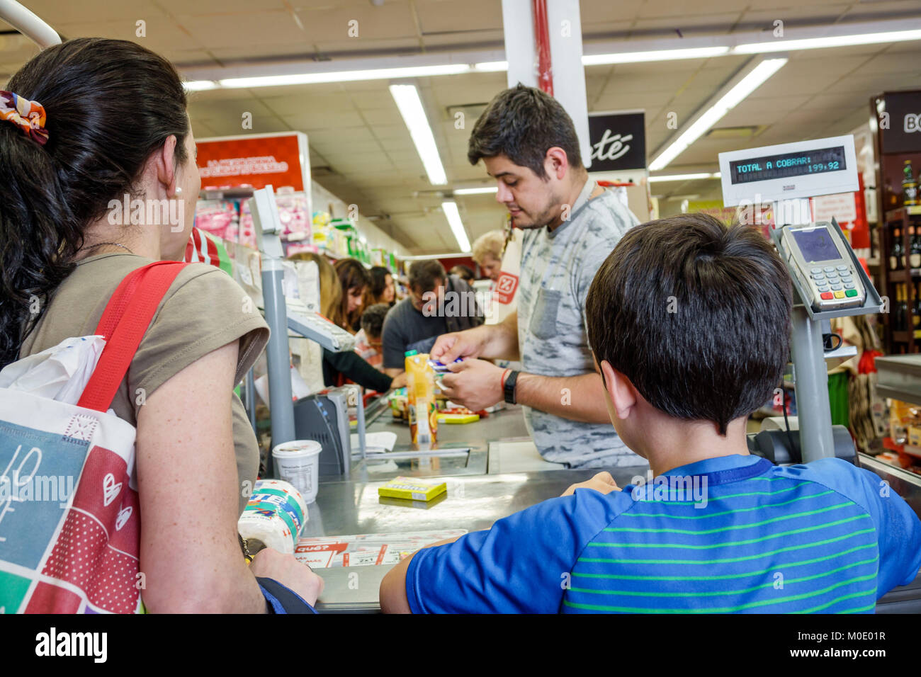 Buenos Aires Argentina San Telmo shopping interior grocery store supermarket food cashier woman boy mother son man - Stock Image