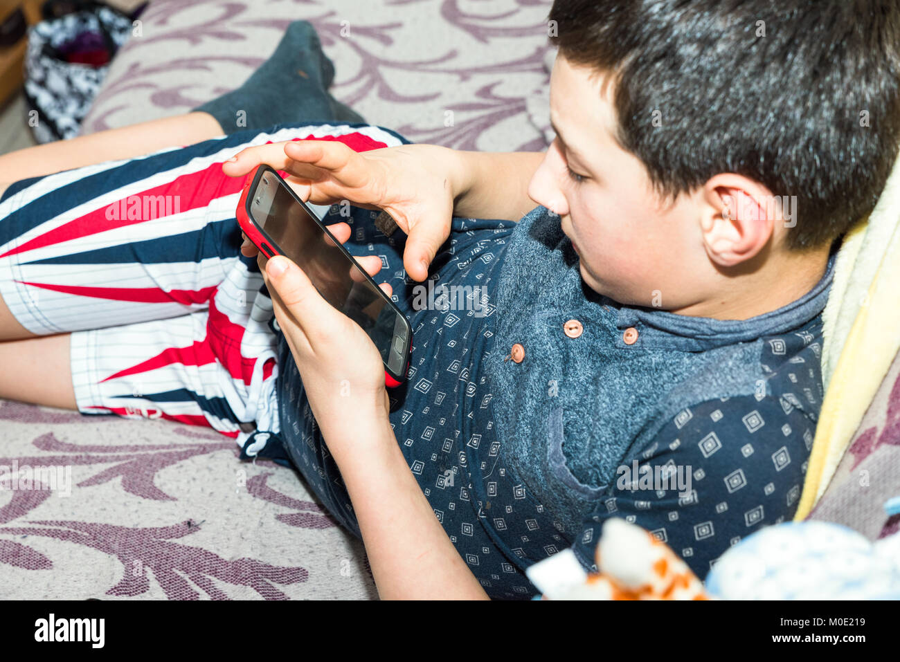 Teen boy holding smartphone and playing games laying on sofa. - Stock Image