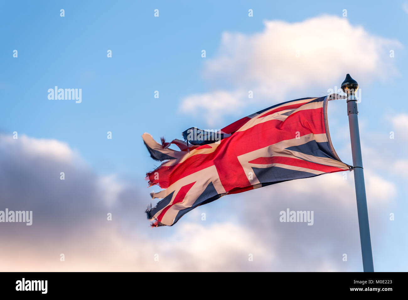 British Flag with torn edges waving over cloudy sky. - Stock Image