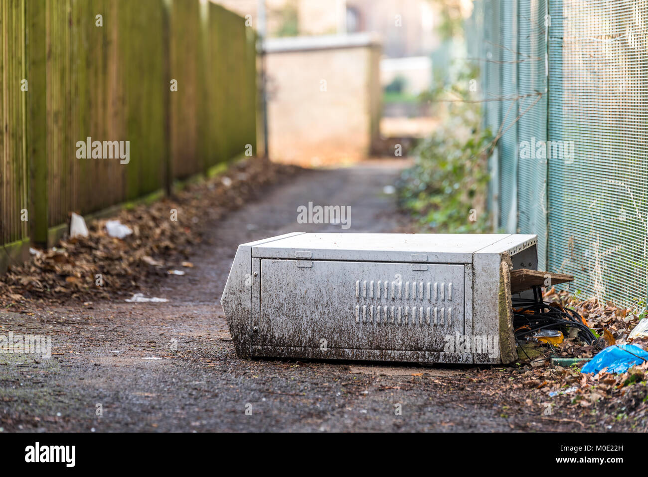 Fallen broken electrical box outdoors on footpath with cable wires exposed. - Stock Image