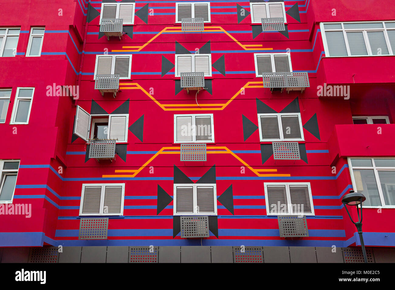 Apartment building painted red, in Tirana, Albania. - Stock Image