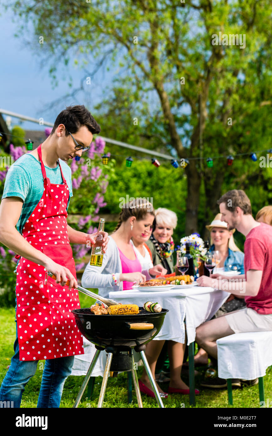 Man grilling meat on garden barbecue party - Stock Image