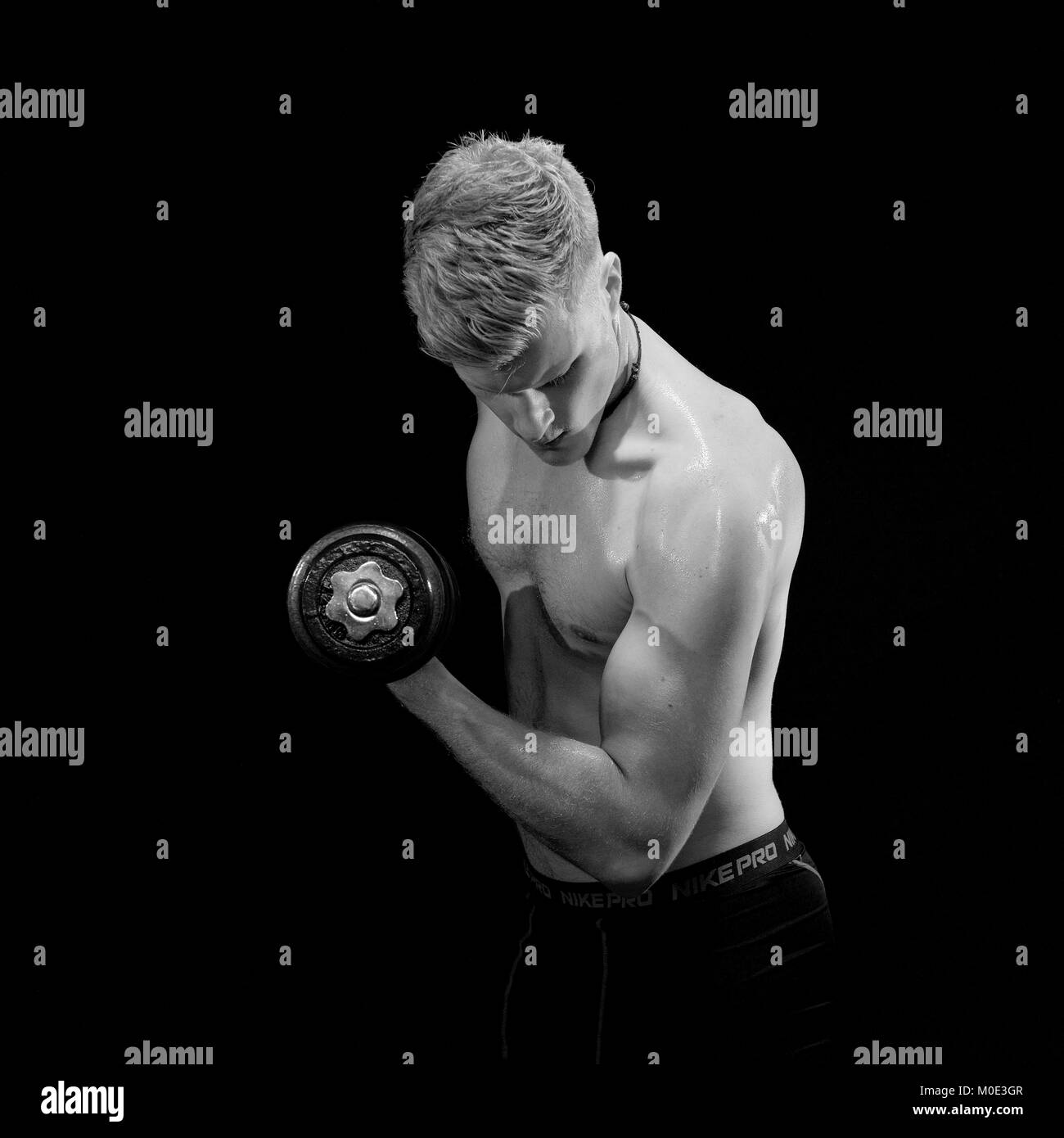 Young man keeping fit against a black background - Stock Image