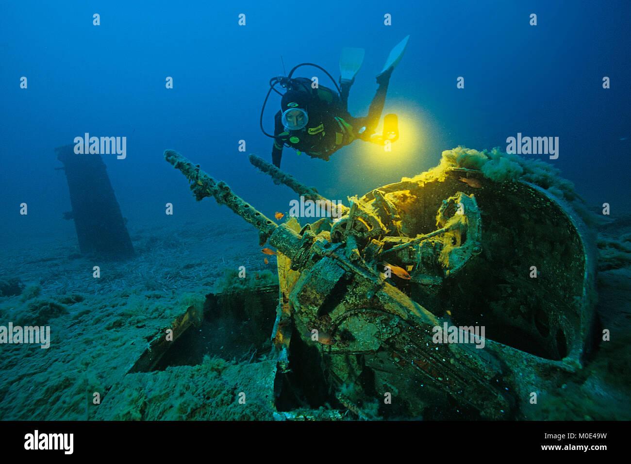 Scuba diver at anti-aircraft gun of a North American B-25 Mitchell bomber, crashed at 2nd world war, Aleria, Corse, Stock Photo