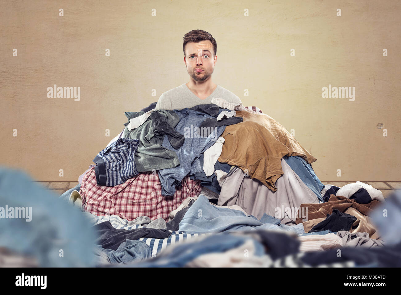 Man in a mess of laundry - Stock Image